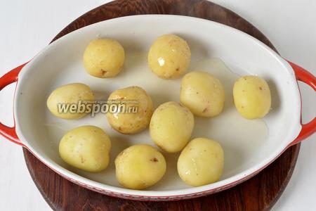 Сцедить отвар, а картофель выложить в жаропрочную форму с 1 столовой ложкой подсолнечного масла. Перемешать, следя, чтобы вся поверхность картофеля была смазана маслом.