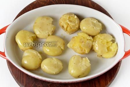 Придавить каждую картофелину донышком стакана таким образом, чтобы она слегка расплющилась. Отправить в духовку при 200°С на 12-15 минут.