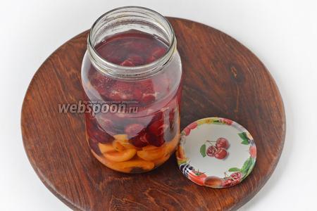 В стерилизованную банку выложить абрикосы, вишню. Залить кипящей водой, накрыть банку крышкой и оставить на 10 минут.