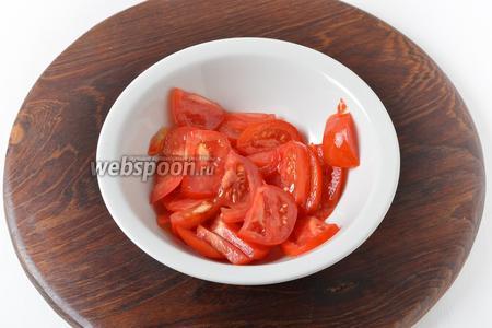 Тем временем промыть помидор и нарезать его тонкими дольками.