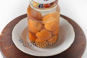 Воду довести до кипения и залить в банки с абрикосами. Прикрыть банки крышками и оставить на 10-12 минут.