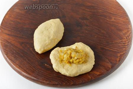 Разделить тесто на небольшие кусочки, сформировать из них лепёшки. На середину лепёшки выложить 1 столовую ложку начинки. Сформировать пирожки.