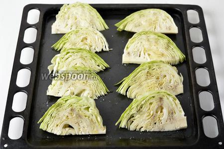Смазать куски капусты с обеих сторон тонким слоем оливкового масла (35 мл), посыпать солью (3 грамма) и чёрным молотым перцем (0,5 грамма). Выложить на противень.