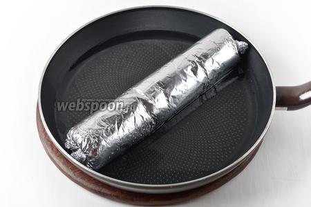 В сковороду до половины высоты налить кипяток. Выложить нашу «колбаску» в сковороду. Готовить под крышкой 10 минут, затем перевернуть на вторую сторону и готовить ещё 10 минут.