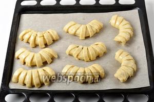 Выложить пирожки на противень с пергаментом, загнуть каждый в виде подковки. Отставленный 1 белок взбить вилкой, кулинарной кисточкой смазать пирожки этим белком сверху. По желанию можно посыпать маком.