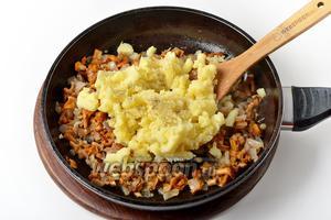 200 грамм картошки очистить и отварить до готовности, тщательно потолочь. Выложить картофельное пюре к лисичкам. Перемешать. Приправить солью (0,5 ч. л.) и чёрным молотым перцем (0,2 ч. л.).