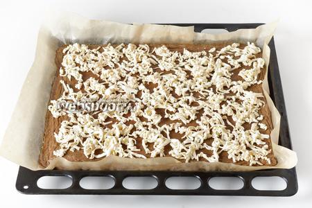 Вынуть форму из духовки. Сверху равномерно натереть на крупной тёрке 200 грамм плавленого сыра.