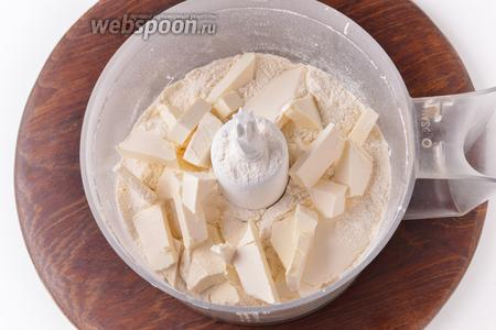 В чашу кухонного комбайна (насадка металлический нож) просеять 300 грамм муки вместе с разрыхлителем (0,5 ч. л.). Сверху выложить нарезанное кусочками холодное сливочное масло (125 грамм). Включить комбайн на 15-20 секунд до образования масляно-мучной крошки.