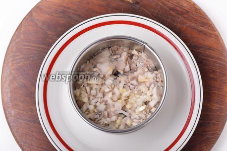 Для формирования салата лучше воспользоваться кулинарным формовочным кольцом. На дно выложить подготовленную рыбу, а на неё — лук. Слегка утрамбовать слои и смазать тонким слоем майонеза.