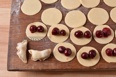 На середину каждого кружка выложить по 2 ягоды замороженной вишни (вишню предварительно не размораживать). Слепить вареники. Опускать порциями, по 6-7 штук, в кипящую подсоленную воду (на 1,5 литра воды 1 ч. л. соли) и готовить 3-4 минуты после того, как вареники всплывут.