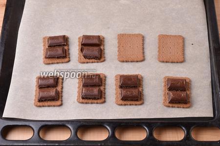 На противень, застеленный пергаментом, выложить крекер (100 г). На каждый крекер выложить кусочки чёрного шоколада (всего 80 грамм). В зависимости от размера крекера, вы можете выложить на него 1 или 2 кубика шоколада.