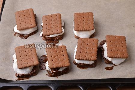 Вынуть противень из духовки и на каждую заготовку сразу выложить сверху ещё по одному крекеру. Слегка нажать на крекер сверху, чтобы крекеры, маршмеллоу и шоколад прилипли друг к другу.