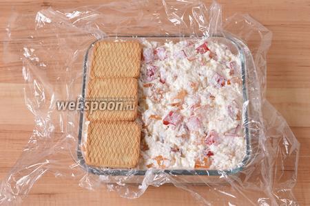 Выложить массу в форму (у меня размером 18х18 см), застеленную пищевой плёнкой. Сверху выложить печенье (100 г).
