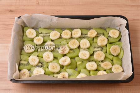 Форму размером 18х28 сантиметров застелить пергаментом. Если вы не уверены в качестве пергамента, его можно смазать очень тонким слоем подсолнечного масла (1 ч. л.). Киви (450 г) очистить и нарезать половинками кружочков. Банан (150 г) очистить и нарезать кружочками. Выложить киви в один слой на дно формы. Сверху разложить кружочки бананов.