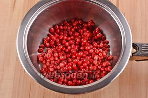 150 грамм ягод замороженной смородины снять с веточек и выложить в кастрюлю.