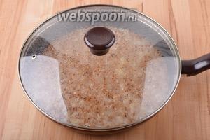 Сковороду плотно закрыть крышкой. Довести содержимое сковороды до кипения, а затем готовить на минимальном огне 17-20 минут. Снять сковороду с огня и оставить на 5-7 минут.