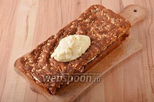 Промазать коржи тёплым кремом. Остатки крема можно использовать для оформления боков торта.