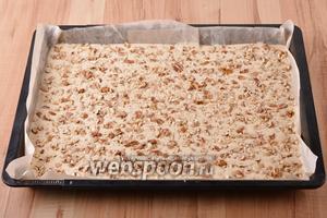 Форму размером 30х40 сантиметров застелить пергаментом. Вылить тесто в форму. Сверху равномерно выложить 1 стакан крупно нарезанных орехов.