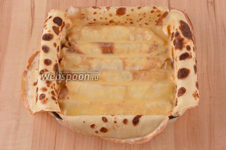 В форму плотно уложить 6 блинных трубочек и полить их половиной сметанно-желтковой смеси.