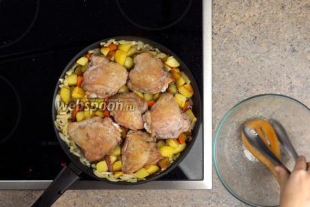 К луку с чесноком выкладываем картофель и морковку, сверху обжаренные кусочки курицы и заливаем всё соусом. Закрываем крышкой и готовим 20-25 минут на медленном огне.