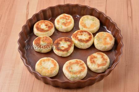 Переложить сырники в жаропрочную форму и запечь в духовке при 180°С 10-12 минут.