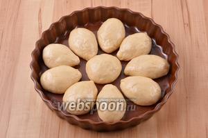 В жаропрочную форму выложить булочки, оставляя между ними некоторое расстояние. Накрыть сверху пищевой плёнкой и оставить в тёплом месте на 25 минут.