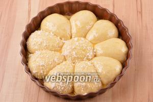1 желток соединить с 5 мл воды, разболтать смесь вилкой и с помощью кулинарной кисти аккуратно смазать булочки сверху. Равномерно посыпать булочки 40 грамм сахара.