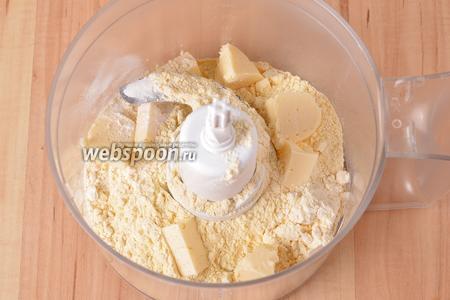 В чашу кухонного комбайна (насадка металлический нож) выложить 110 грамм просеянной кукурузной муки, 2 грамма соли, 3 грамма разрыхлителя и 50 грамм нарезанного кусочками очень холодного сливочного масла. Включить комбайн на 1 минуту для того, чтобы образовалась мелкая крошка.