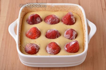Форму (размером 15х15 сантиметром) смазать 5 мл подсолнечного масла. Выложить тесто в форму. Сверху в тесто воткнуть 100 грамм замороженной клубники.