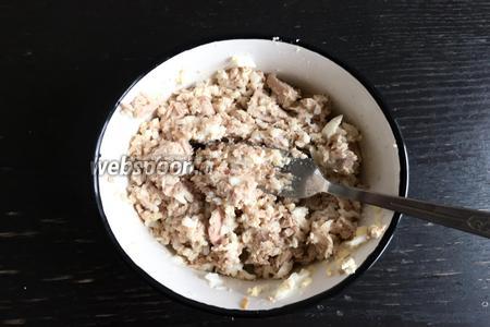 Содержимое из банки с тунцом выкладываем в тарелку и перемешиваем, вылив лишнюю жидкость из банки. Смешиваем вилкой тунец и натёртые яйца.