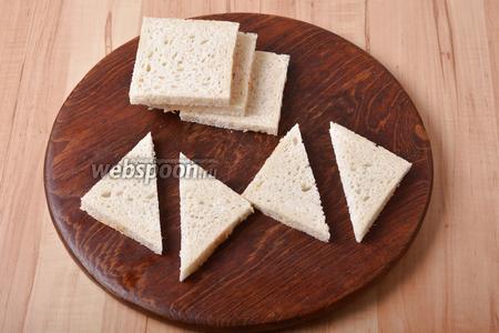 У 8 ломтиков тостового хлеба обрезать корки. Разрезать каждый кусочек на 2 треугольника.