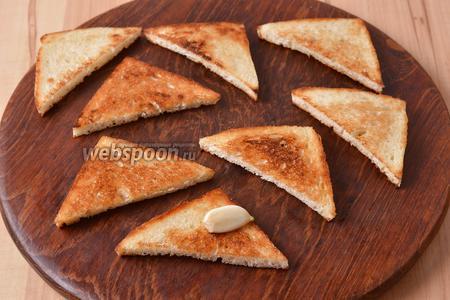 Переложить кусочки хлеба на тарелку или разделочную доску и натереть с одной стороны очищенным зубчиком чеснока (2 шт.).