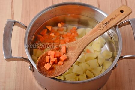 100 грамм моркови очистить, нарезать небольшими кусочками и выложить в кастрюлю.