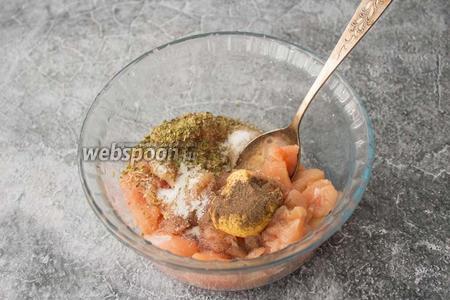 Выложите кусочки курицы в миску, добавьте соль по вкусу, перец (1 щепотку), орегано (1 ч. л.) и 1 чайную ложку горчицы.