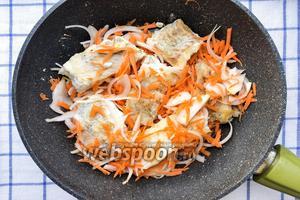 На дно сковородки выкладываем по половине нарезанного лука и моркови, затем слой рыбы, и сверху вторую половину лука и моркови.