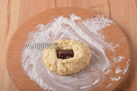 Разделить тесто на 6 частей. На середину каждой части теста выложить дольку шоколада. Мокрыми руками завернуть шоколад внутрь и сформировать булочку.