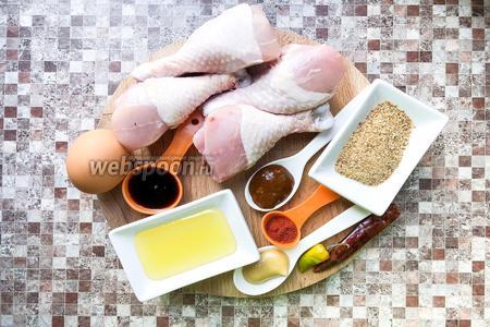 Для приготовления рецепта возьмите куриные голени, яйцо, соевый соус, мёд, аджику, горчицу, свежий перец чили, сухой перец чили, копчёную паприку, подсолнечное масло, панировочные сухари.