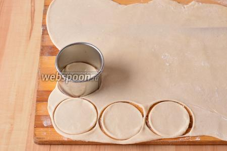 Раскатать тесто пластом, толщиной 1,5 миллиметра, и вырезать кружки диаметром приблизительно 6 см.