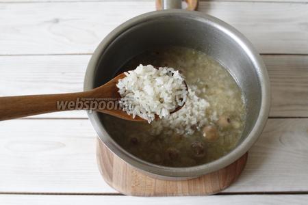 Готовность маша проверяется по его раскрытости. Как только маш будет готов, промыть рис (150 г) и добавить в кастрюлю. Вода должна покрывать рис примерно на 0,5 см в высоту, поэтому если у вас сильно выкипела вода, то необходимо будет её добавить. Посолить (5 г). Во время варки рис не перемешивать, дождаться пока испарится вся жидкость, убавить огонь и томить рис под крышкой до готовности. Когда рис будет готов, перемешать его.
