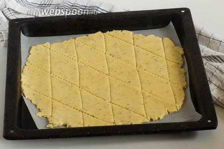 Раскатайте тесто на листе пергаментной бумаги в пласт толщиной 3-4 мм. Чем тоньше будет тесто, тем быстрее оно подрумянится и тем более рассыпчатым оно будет. Нарежьте тесто произвольно на кусочки.