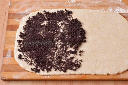 Разделить тесто на 2 части. Раскатать каждую часть в прямоугольный пласт толщиной 0,5-0,6 см. Смазать их по всей площади маковой начинкой.