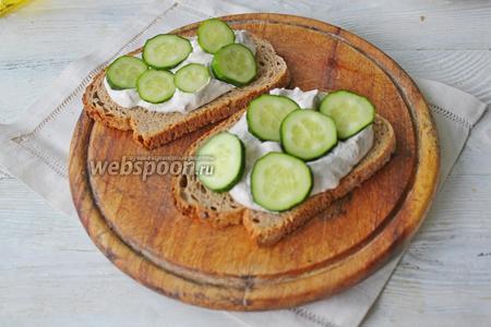 Соберите сморреброд. На подсушенный хлеб выложите творожную массу, поверх распределите кружочки свежего огурца.