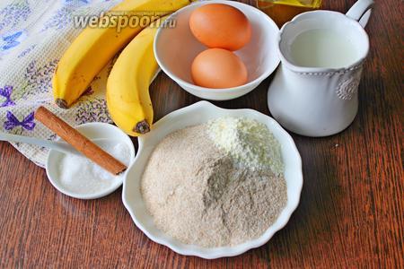 Подготовьте все необходимые ингредиенты: куриные яйца, цельнозерновую муку, соль, сахар, корицу, разрыхлитель, молоко комнатной температуры, спелые бананы и подсолнечное масло.