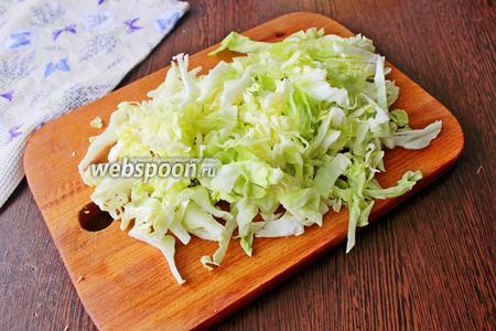 Молодую капусту, весом около 1 кг, нарежьте тонкой соломкой.