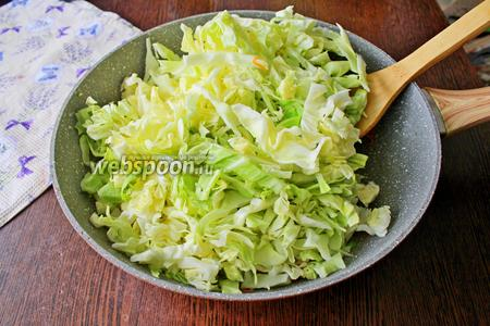 Добавьте нашинкованную капусту, перемешайте и готовьте ещё 2-3 минуты.