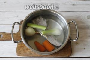 Мясо переложить в кастрюлю, заполнить её чистой питьевой водой (2 литра), довести до кипения. Как только вода закипит, убавить огонь, добавить в кастрюлю овощи: репчатый лук, стебли сельдерея и морковь.
