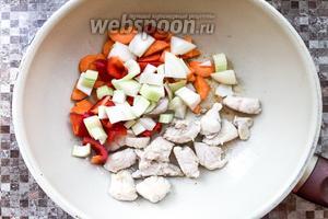 Достаточно крупно нарежьте 1 морковь, 1 луковицу, 1 болгарский перец, 1 стебель сельдерея. Добавьте к курице и обжаривайте пару минут.