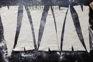 Разделим тесто на равные треугольники при помощи ножа. В широкой части сделаем небольшие надрезы.