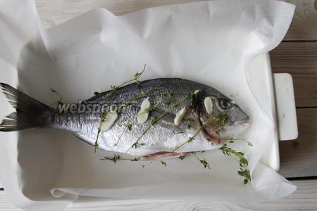 Веточки свежего тимьяна (10 веточек) уложить в брюхо рыбы и разложить сверху. 1 зубчик чеснока разрезать на тонкие слайсы и также положить в брюхо рыбы и сверху.