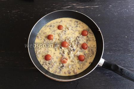Порезать 4 помидора черри пополам и добавить к омлету, накрыть крышкой и потушить ещё 2 минуты.